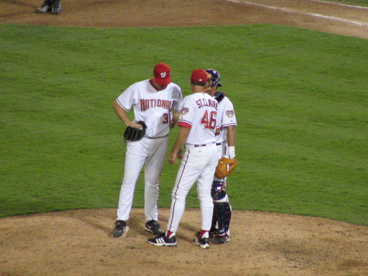 A meeting on the pitchers mound during a baseball game