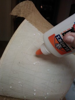 A little Elmer's glue holds fabric in place while attaching it to the frame and adding trim.
