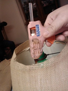 Firmly attach fabric with a hot glue gun.  Low temp glue will soften under the heat of a bulb.