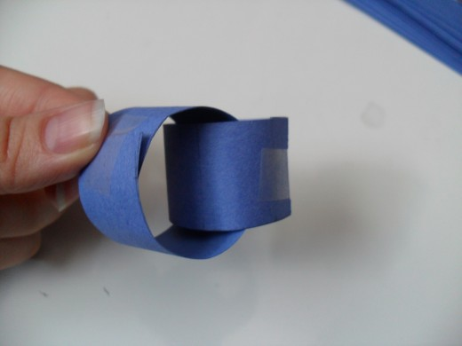 How to make a paper chain: Thread another strip through the first one and glue that loop closed