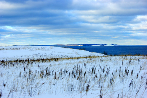 Looking across Sleeping Bear Dunes, with dune grass showing through the snow and  North Manitou Island sitting seven miles off shore in Lake Michigan.