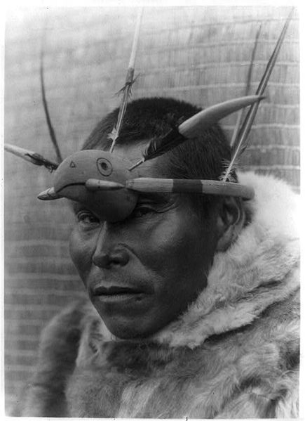 A Nunivak Cup'ig man with raven maskette. The raven (Cup'ig tulukarug) is Ellam Cua or Creator god in the Cup'ig (and Yupiaq) mythology