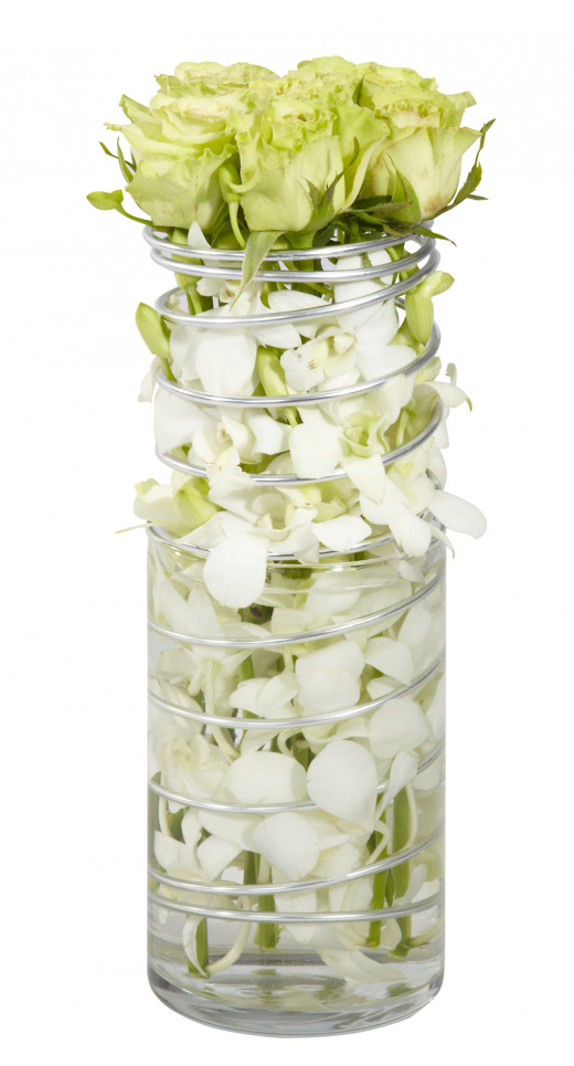A narrow cylinder vase, filled with stems of white dendrobium orchids, wrapped with wire and with pale green roses on top.