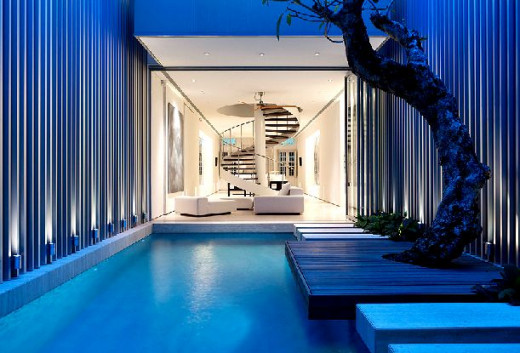 Indoor swimming pool within the living room - blue pool room and white ultra modern living room with silver spiral staircase and corrugated steel walls in the court yard