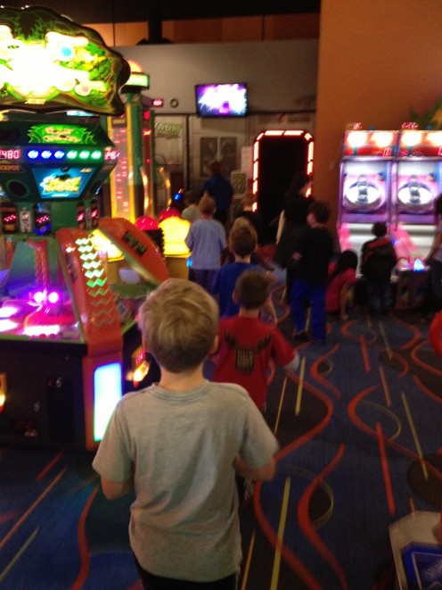 Kids in a row at arcade bowling birthday party