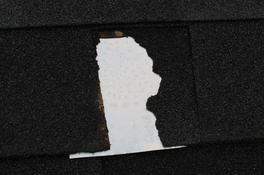 Small section of metal flashing cut and slid under the upper shingle protects the open hole until repairs can be made.