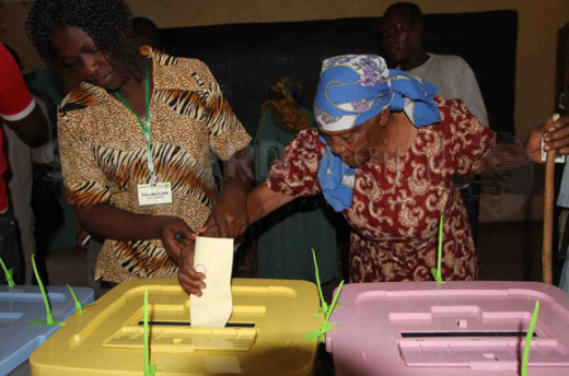 An elderly woman being assisted to vote by IEBC officials