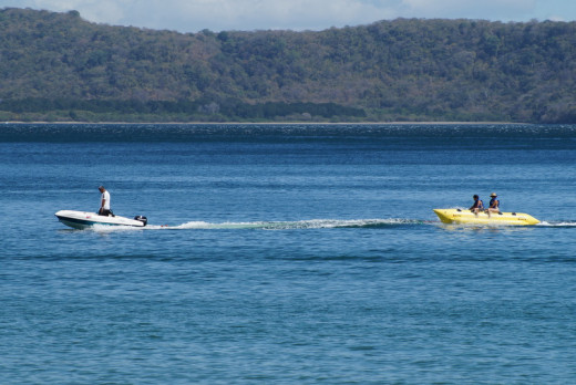 A banana raft being towed behind a boat.  A common entertainment of most of the popular beaches.