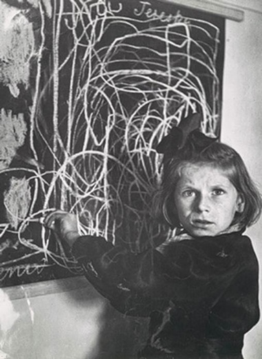 """Tereska, a child in a residence for disturbed children, grew up in a concentration camp. She drew a picture of """"home"""" on the blackboard,Poland, 1948."""