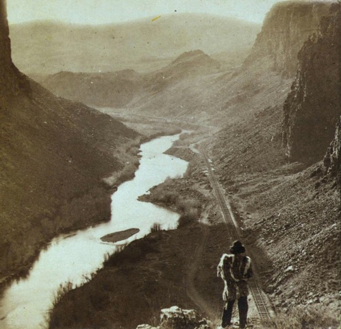 A Native American looks down at a newly-completed section of the transcontinental railroad. Nevada, about 1868.