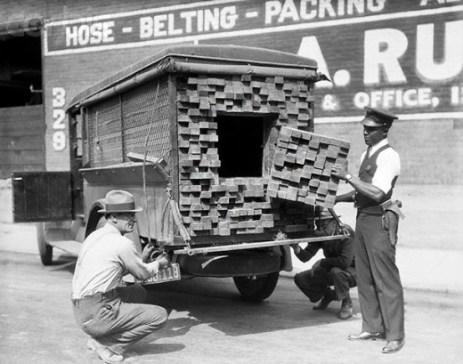 "Alerted by the smell of a broken bottle of liquor, Federal Agents inspect a ""lumber truck"". Los Angeles, 1926."
