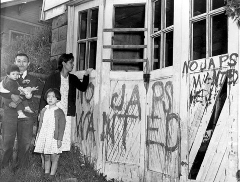 A Japanese family returning home (Seattle, Washington) from a relocation center camp in Hunt, Idaho on May 10, 1945.