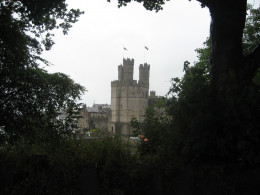 The towers of Caernarvon framed by trees in a nearby park.