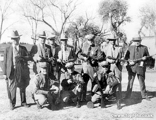 The police officers who aided in the capture of the Dillinger gang in Tucson Arizona shown above with five sub-machine guns, bullet proof vests, revolvers and ammunition taken from members of the gang of Bank Robbers and escaped convicts. From left