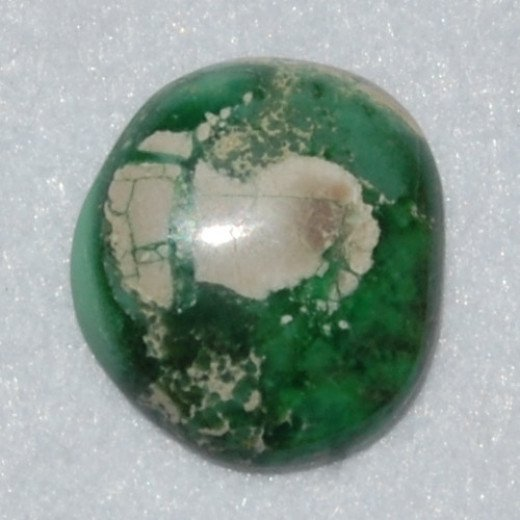 Freeform cabochon made of Variscite from Lucin Utah showing typical white-grey matrix.