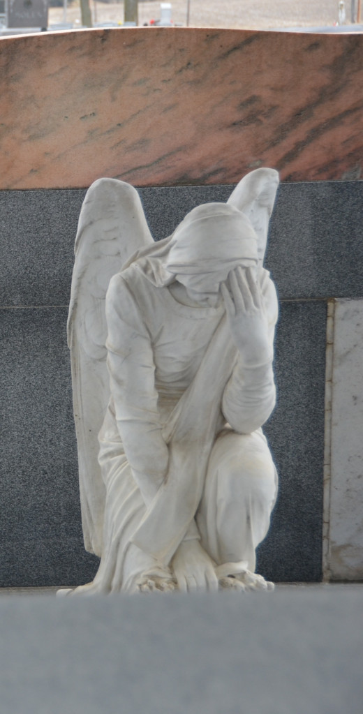 Sarah Davis depicted in prayer with angel wings at the foot of John's grave