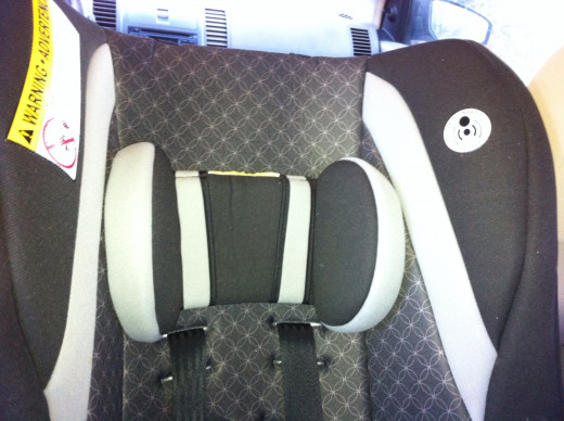 Safety pictures on top area of car seat.