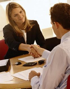 Man and woman shaking hands before an interview.