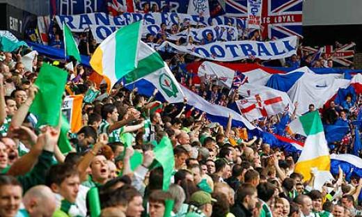Celtic and Rangers fans holding flags aloft
