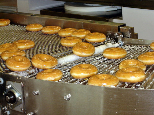 Krispy Kreme conveyor belt. Mass produced doughnuts.