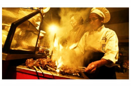 Doña Grimanesa Vargas grilling her anticuchos on a barbecue.