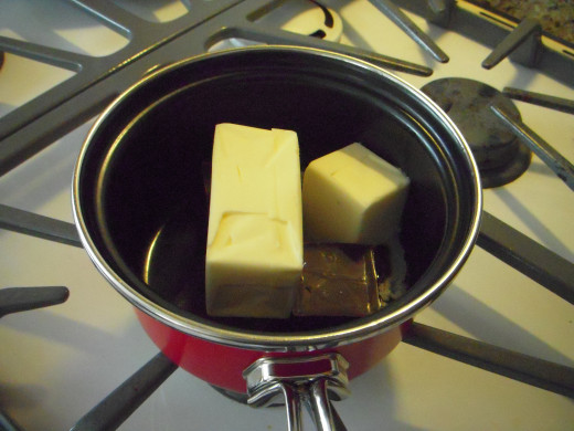 Place butter and chocolate together in a small pan over very low heat. You will need to watch and stir constantly to ensure the chocolate doesn't burn and curdle.