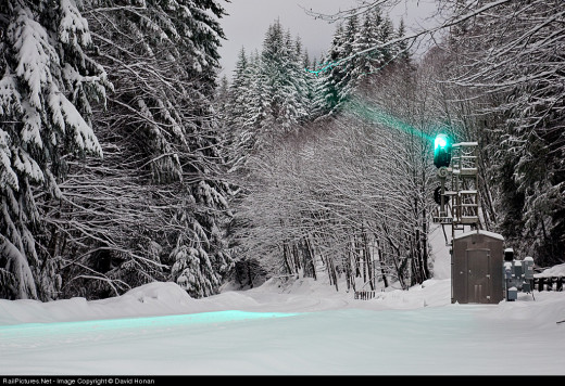 A green signal indicating clear track ahead in this wintery scene.