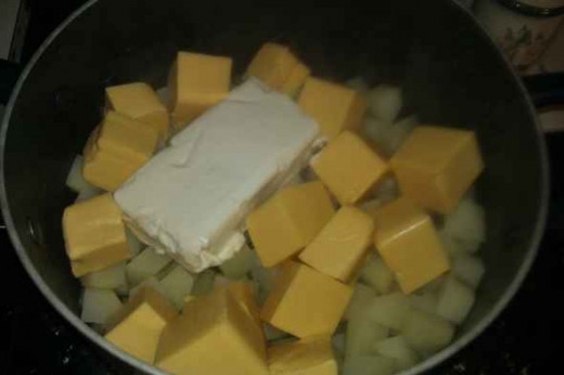 Remove the cooked potatoes from the heat. Add the cream cheese and Velveeta cheese to the potato pot. Tip: the cheese melts faster if cubed first. After the cheese is melted, you can add the rest of the ingredients.