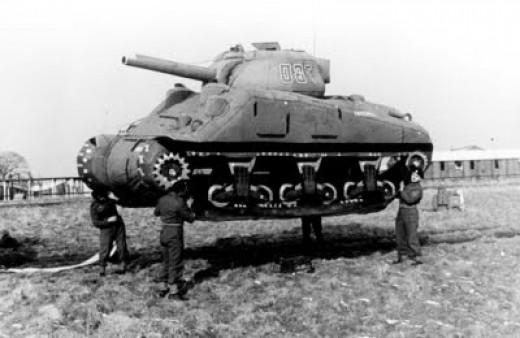 Four men lifting an inflatable tank