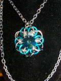 This Japanese 12 in 2 Necklace is made with Light Blue and Silver anodized aluminum rings and has a stainless steel lobster clasp. This hand woven pendant with basic silver chain is approximately 18 inches long.