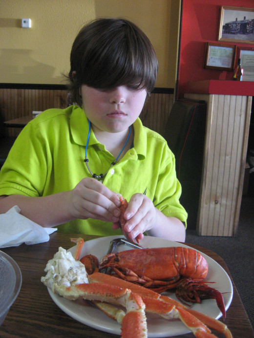 My grandson, attacking crab legs, crawfish, and a lobster.