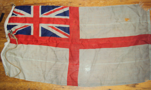 Here's the ensign that my father saved from his sinking LCI. You can see a few bullet rounds have gone through it plus a mortar shell has blown one corner off it.