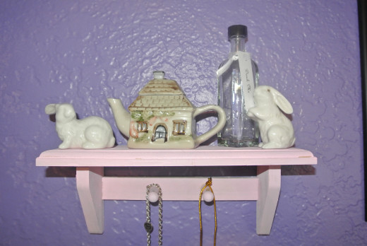 "I reused these smaller glass bottles to represent the ""drink me"" bottles for the Alice in Wonderland theme.  I found the small teapot house at an antique store, too.  It reminded me of the house that became tiny when Alice grew inside of it."