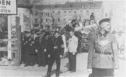 This picture includes both German and Jewish police guard an entrance to the Łódź Ghetto.