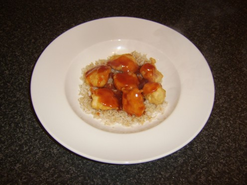 Deep fried battered chicken balls served on a bed of fried rice with sweet and sour sauce