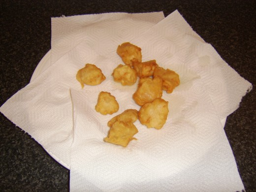Deep fried chicken is drained on kitchen paper