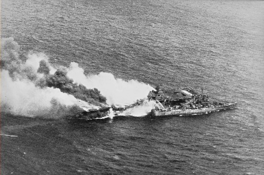 The USS Pittsburgh comes alongside the burning carrier to fight the fires and assist in any way it can Source: Wikipedia (Public Domain)