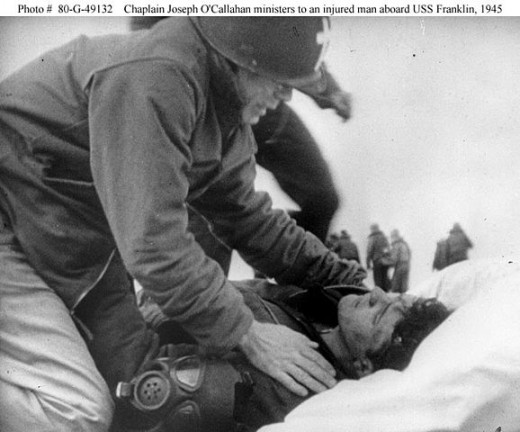 Fr. O'Callahan comforts a wounded sailor abourd the USS Franklin. The sailor would survive his injuries