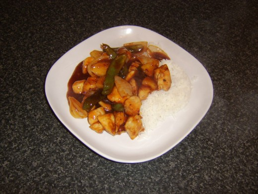 Sweet and sour chicken with boiled rice is ready to eat