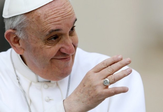 Pope Francis who is a Jesuit, with a cross on his ring.