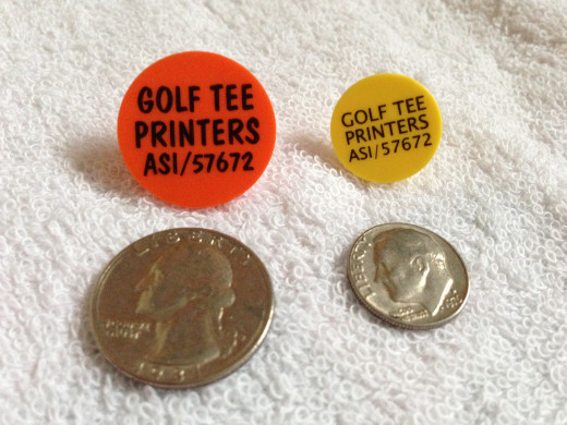 Golf ball markers generally come in two sizes, quarter (left) and dime (right), following golfers' practice of using coins to mark.