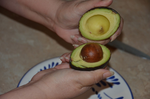 Gently remove the top half of the avocado.  The lower half with contain the pit.