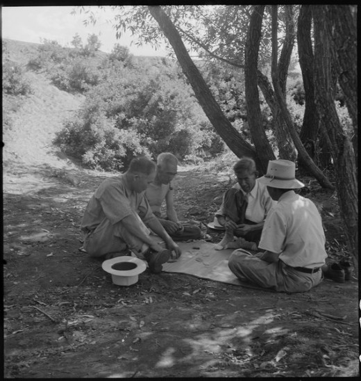 Dorothea Lange, Manzanar Relocation Center, Manzanar, California. Evacuees enjoying games under the shade of trees near the creek which flows through the desert on the border of this War Relocation Authrority center. Department of the Interior. War R
