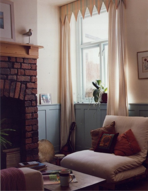 Living room with painted panelling and exposed brickwork.