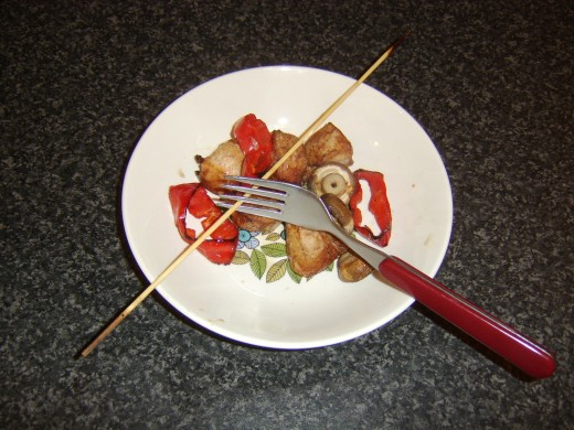Chicken and vegetables are slid from skewer