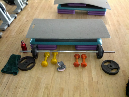 Set up for class includes a step bench with risers, barbell and weight plates, mat, and dumbells.