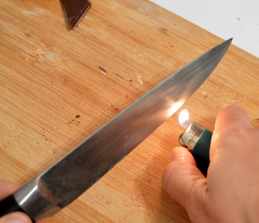 Move a lit lighter along the cutting portion of your knife to heat it.