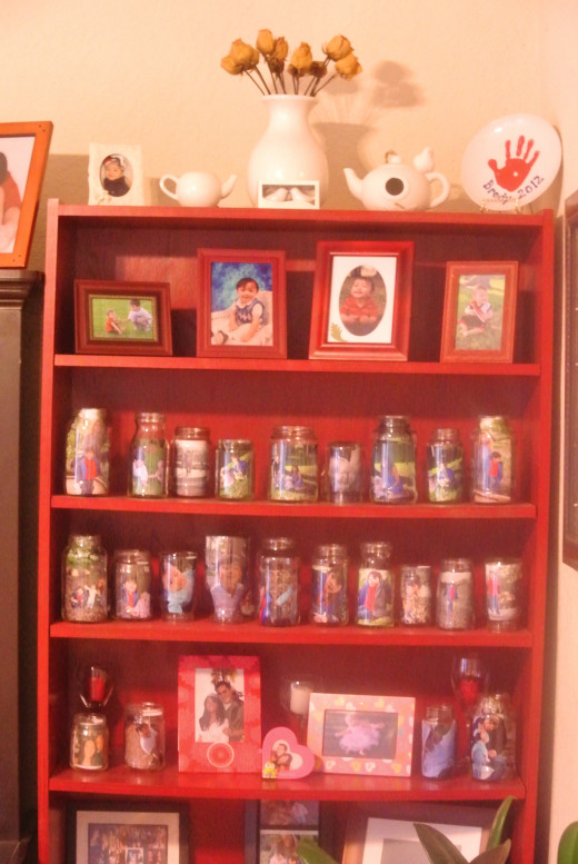 I bought this bookcase from craigslist and repainted it  a cherry red.  I reused glass jars to hold photos; fun way to recycle the jars and they take less space then picture frames so I was able to display more photos in the case.