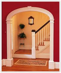curved threshold or arched interior entry way leading to wooden stairs