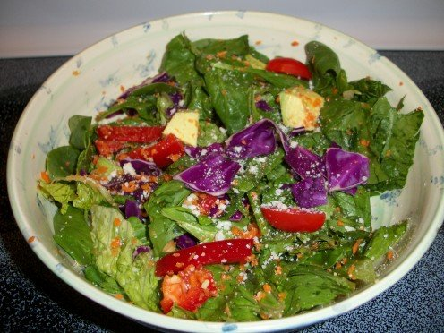 This healthy salad contains a few Superfoods such as spinach, romaine, avocado, tomato, and red cabbage.